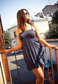 Woman in short dress leaning against metal railings on stairs — Stock Photo