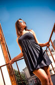 Tanned latin girl in short dress leaning against metal railings — Stock Photo