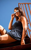 Sexy tanned girl in sunglasses sitting on metal stairs outdoor — Stock Photo