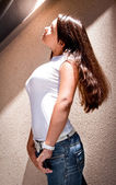 Girl with big breast and long hair leaning against wall outdoor — Stock Photo