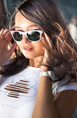 Portrait of sexy brunette girl putting on sunglasses at windy day — Stock Photo
