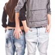 Handsome man holding hand in back pocket of girlfriends jeans — Stock Photo