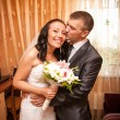 Portrait of young groom kissing bride in room — Stock Photo #42117339