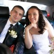 Married couple sitting on back seat of car and looking at camera — Stok fotoğraf