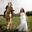 Photo of bride pulling horse by rein with groom riding in saddle — Stock Photo #42117573