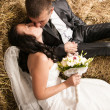 Portrait of beautiful bride and groom kissing on stack of hay — Stock Photo