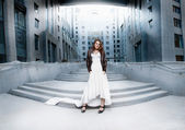 Woman in long white dress standing on stairs against modern building — Stock Photo