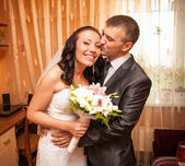 Portrét mladého ženicha líbání nevěsty v místnosti — Stock fotografie