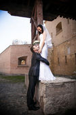 Groom hugging beautiful bride standing on high parapet — Stock Photo