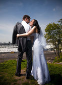 Beautiful newly married couple hugging on top of hill — Stock Photo
