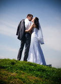 Married couple standing on top of hill against blue sky — Stock Photo