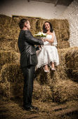 Married couple looking at each other at stable with stack of hay — Stock Photo