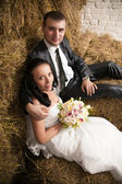 Portrait of bride and groom hugging on hay at stable — Stock Photo
