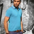 Sexy tanned man in blue shirt posing against concrete wall — Stock Photo #42160001
