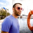 Man in sunglasses standing at seaport against yachts and lifebuoy — Stock Photo