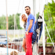 Handsome man and sexy girl standing on yacht at seaport — Stock Photo #42160075