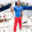 Latin man in sunglasses standing on white yacht — Stock Photo