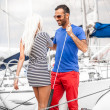 Stock Photo: Latin man inviting sexy blonde woman on his yacht