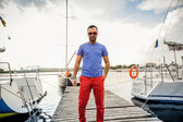 Stylish man posing on pier against sea and yachts — Stock Photo