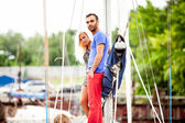 Handsome man and sexy girl standing on yacht at seaport — Stock Photo