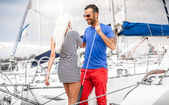 Latin man inviting sexy blonde woman on his yacht — Stock Photo