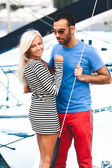 Latin man hugging sexy blonde woman on yacht — Stock Photo