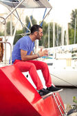 Latin man sitting on deck of red yacht at seaport — Stock Photo