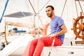 Latin man sitting on yacht deck — Stock Photo