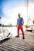 Portrait of handsome man standing on pier against white yachts — Stock Photo