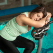 Brunette woman relaxing after training on exercise bike — Stock Photo #42353303