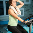 Woman training on exercise bike against swimming pool — Stock Photo