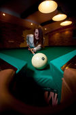 Brunette woman aiming with cue at billiard ball — Stock Photo