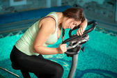 Brunette woman riding exercise bike at fitness club — Stock Photo