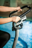 Shot woman riding exercise bike — Stock Photo