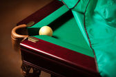 Ball in billiard pocket on partly covered table — Stock Photo
