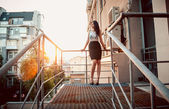 Woman standing on balcony with metal railings at sunset — Stock Photo