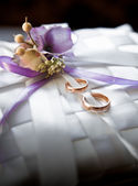Wedding rings lying on satin cushion decorated with flowers — Stock Photo