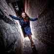 Woman posing between two brick walls at night — ストック写真