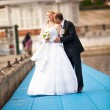 Portrait of groom kissing bride on pier near river — Stock Photo #42567703