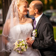 Bride and groom looking at each other on street — Stock Photo