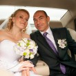 Bride and groom sitting on back seat of car — Stock fotografie #42567773