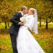 Bride and groom kissing at autumn park — Stock Photo