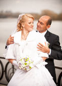 Closeup portrait of mid-aged bald groom hugging bride from back — Stock Photo