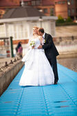 Portrait of groom kissing bride on pier near river — Stock Photo