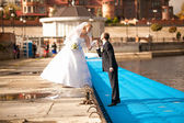 Bride and groom kissing on pier at sunny day — Stock Photo