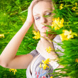 Blonde woman lying on grass with yellow flowers — Stock Photo #42580549