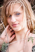 Beautiful smiling blonde woman leaning against bushes — Stockfoto