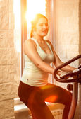 Brunette woman riding exercise bike at sunny day — Stock Photo