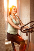 Active slim woman riding exercise bike at gym — Stock Photo
