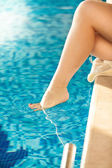 Shot of woman dangling sexy leg in swimming pool — Stock Photo